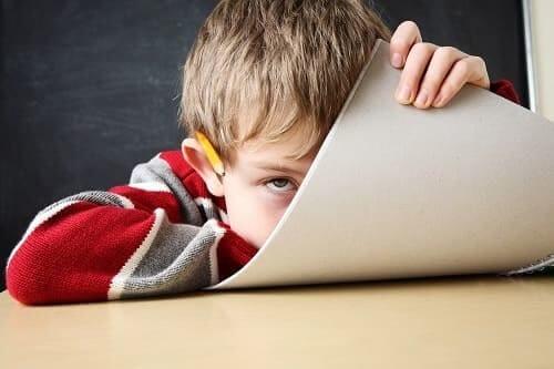 Мальчик закрывается листом тетради