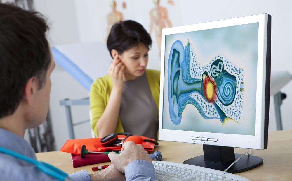 Женщина жалуется врачу на шум в ушах