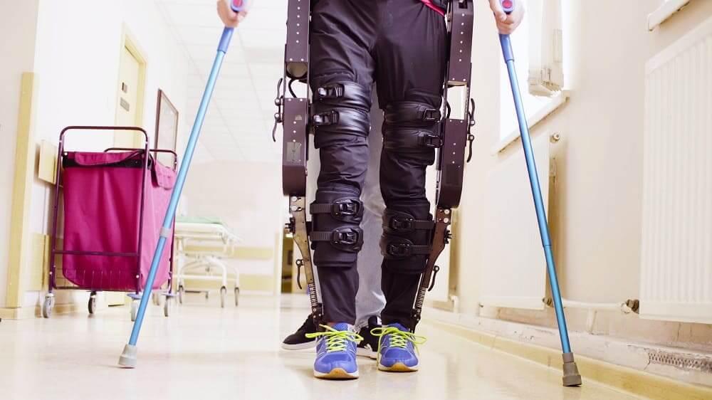 Мужчина с экзоскелетом на ногах и с костылями