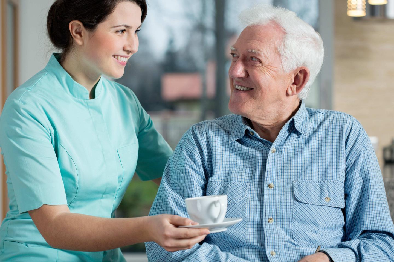 Девушка подает чашку на блюдце пожилому мужчине