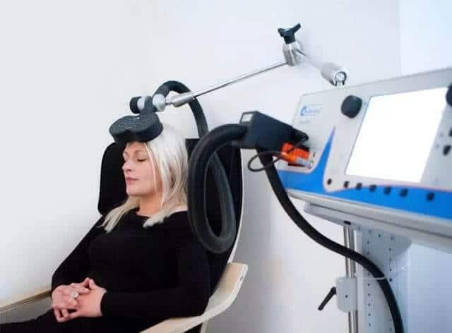 Девушка с закрытыми глазами на процедуре транскраниальной магнитной стимуляции