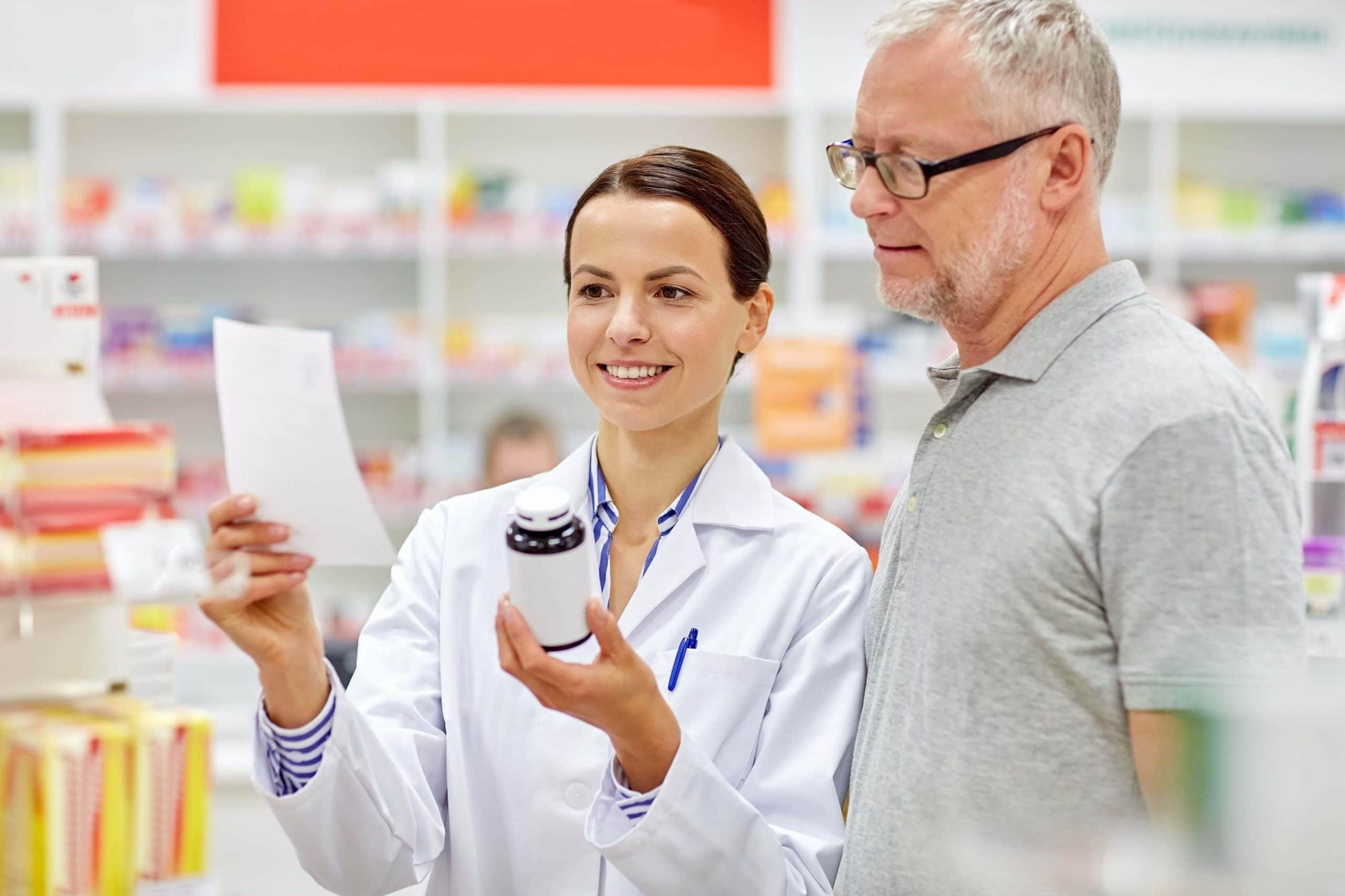 Фармацевт в аптеке показывает мужчине лист и пузырек с лекарством