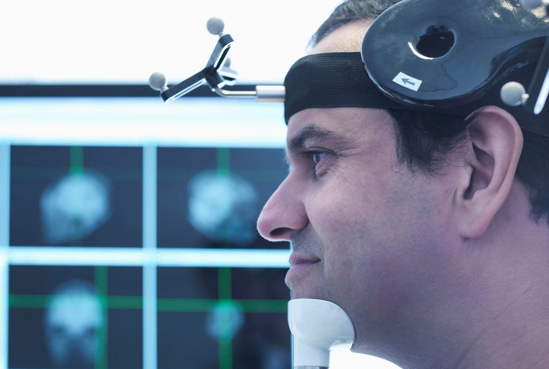 Голова мужчины с катушкой ТМС на фоне монитора
