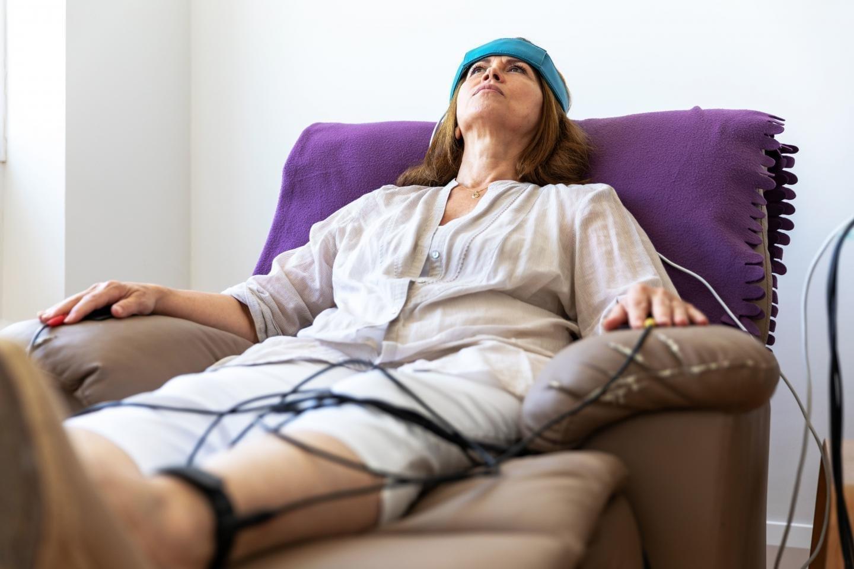 Женщина проходит процедуру БОС, лежа в кресле