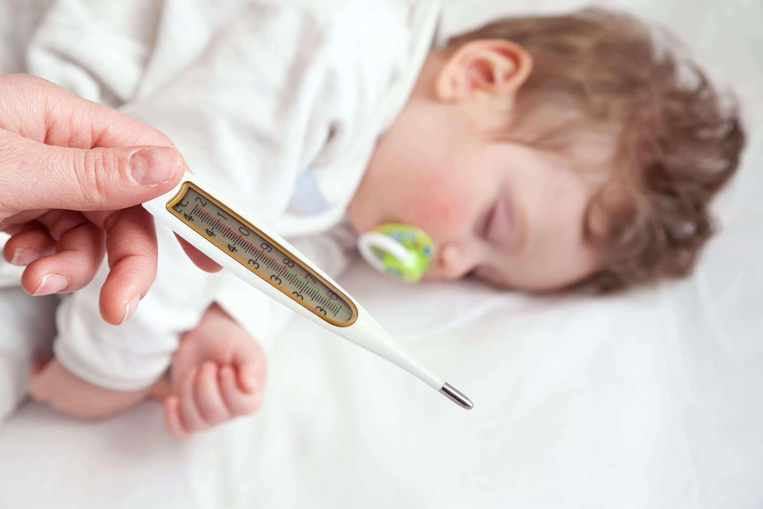 ребенок спит, мама измеряет температуру