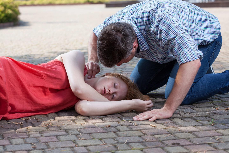 молодая девушка потеряла сознание, мужчина уложил ее на бок , оказывает помощь