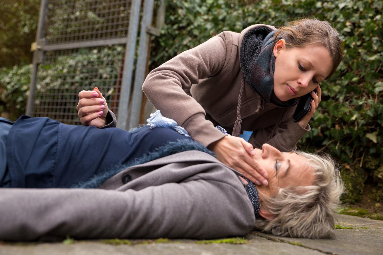 женщина потеряла сознание, молодая девушка ей помогает