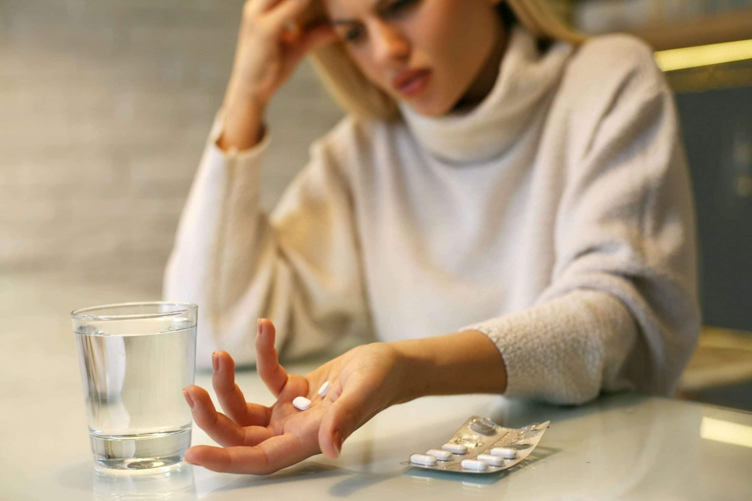 девушка собирается принять таблетки