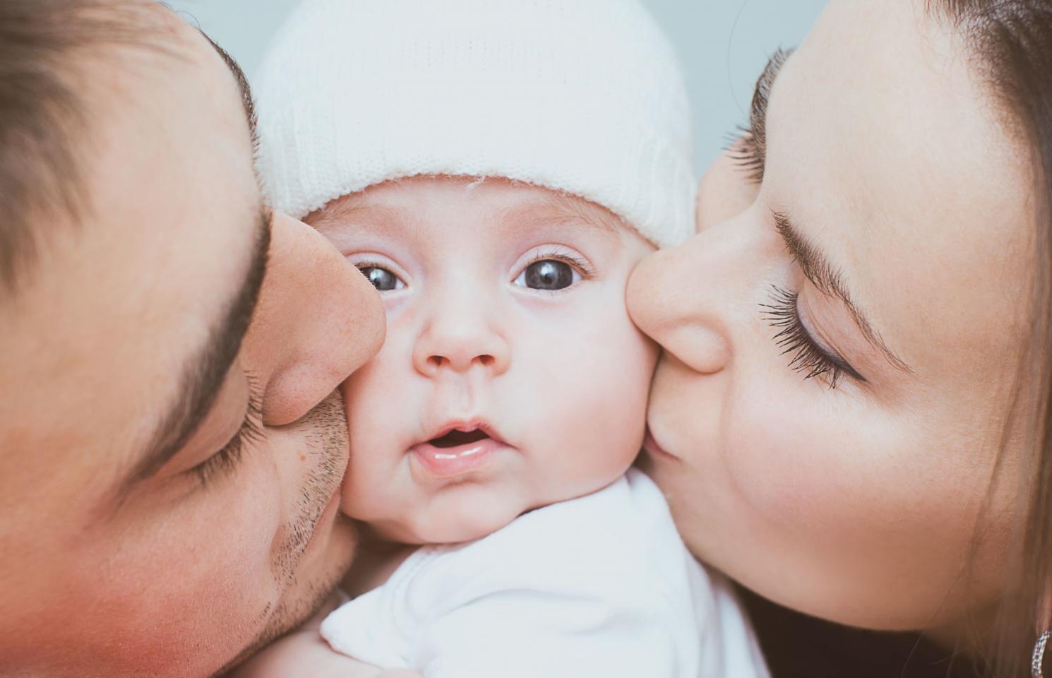 мама и папа целуют ребенка