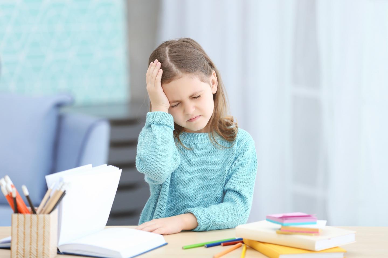 девочка учит уроки , заболела голова