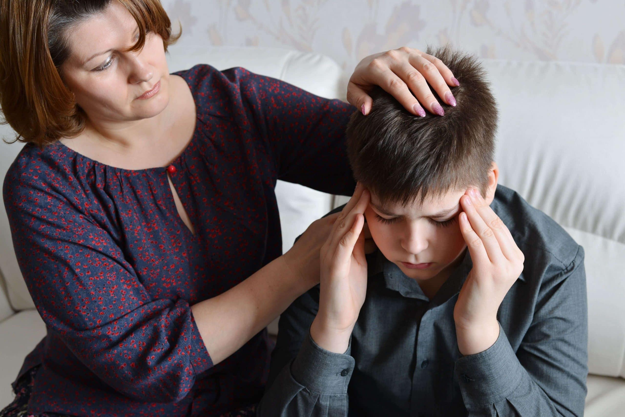 мальчик жалуется на головную боль , рядом мама