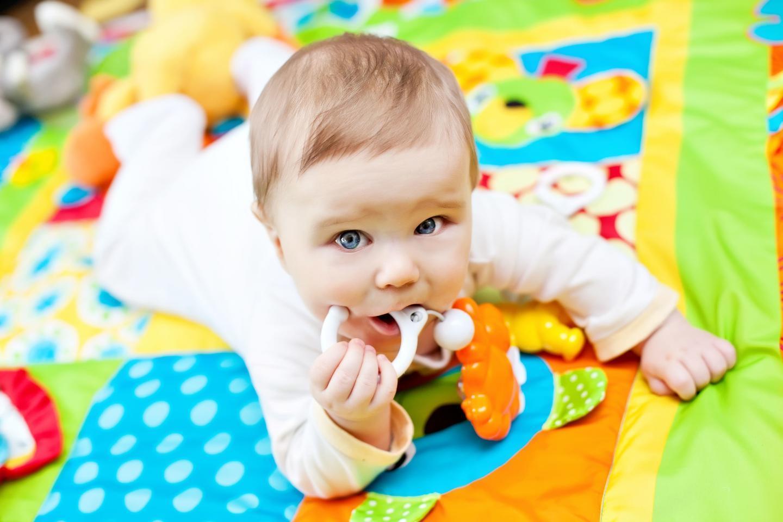 ребенок лежит на животе , играет с игрушками