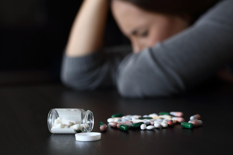 молодая девушка , перед ней рассыпан флакон с препаратами