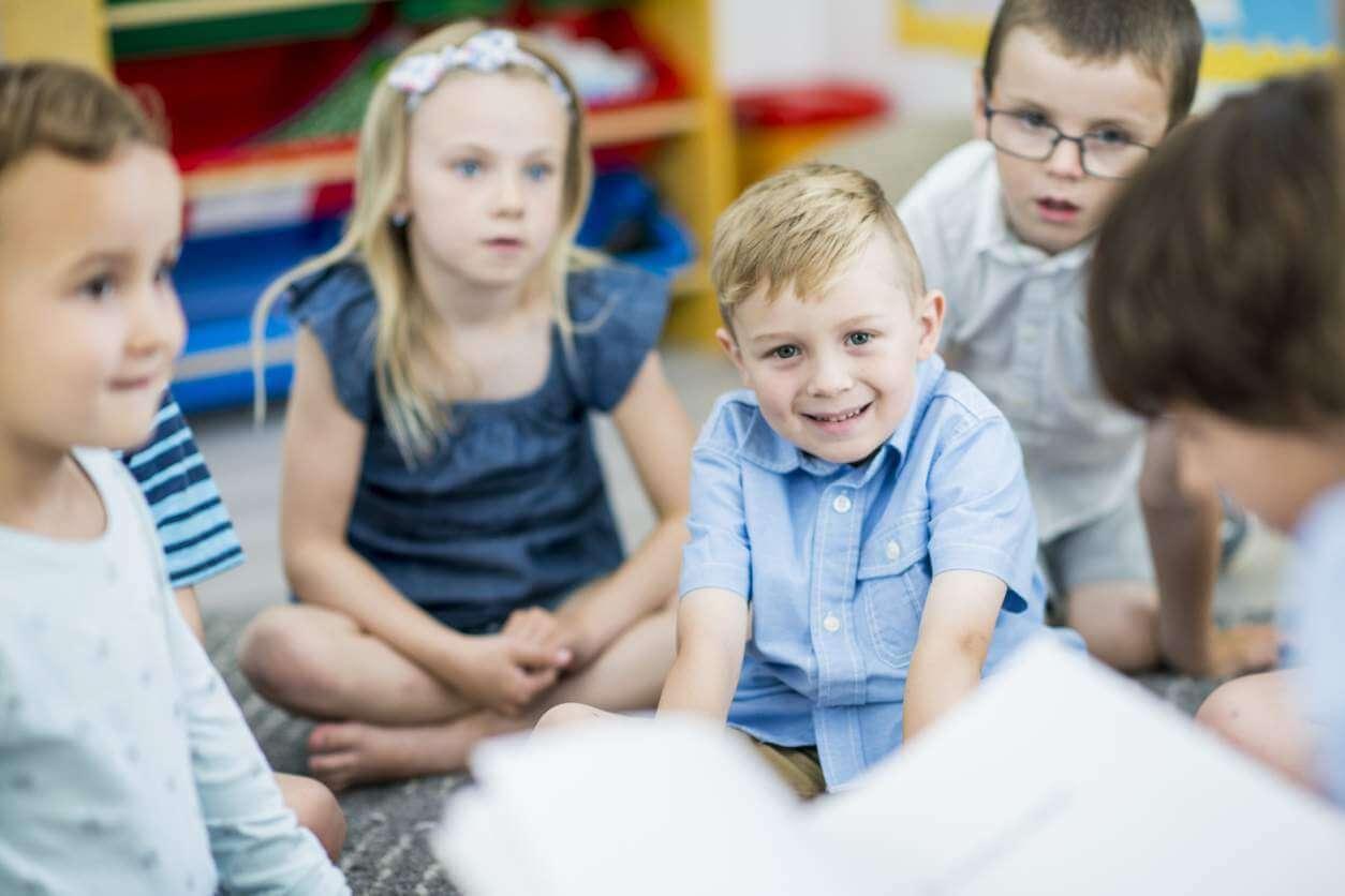 Дети на занятии в группе сидят на полу