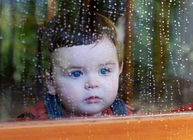 Маленький ребенок смотрит в окно с каплями дождя