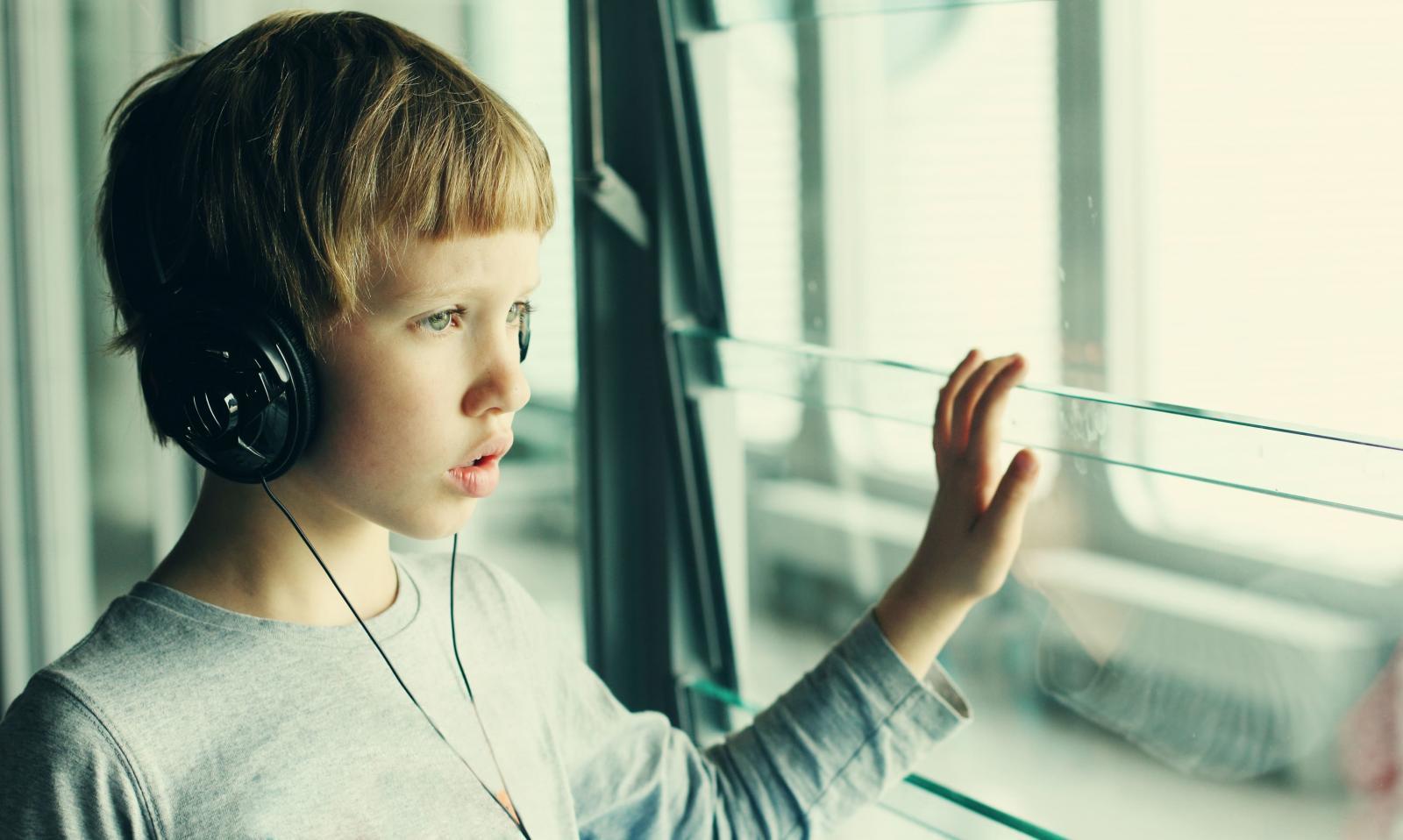 мальчик в наушниках смотрит в окно