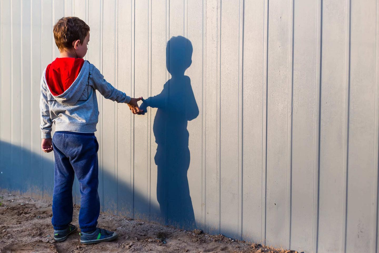 мальчик трогает свою тень