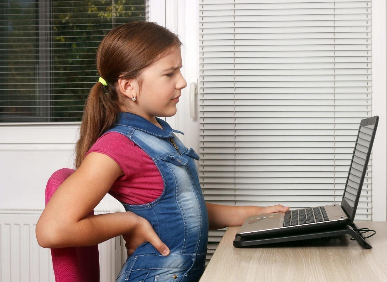 девочка неправильно сидит за компьютером из-за чего боль в спине