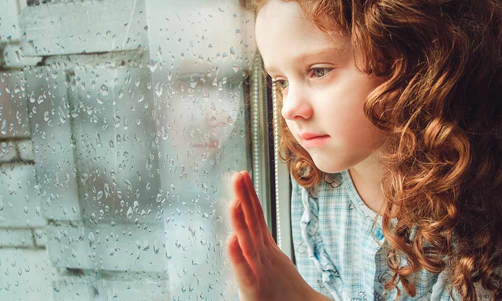 Девочка смотрит в окно, капли дождя