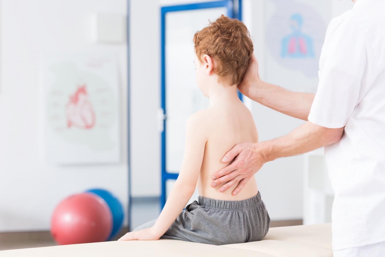 врач осматривает спину ребенку