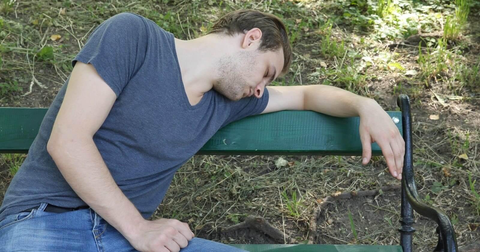 мужчина уснул на скамейке в парке