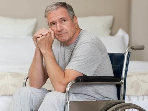 Пожилой человек с болезнью Паркинсона в коляске