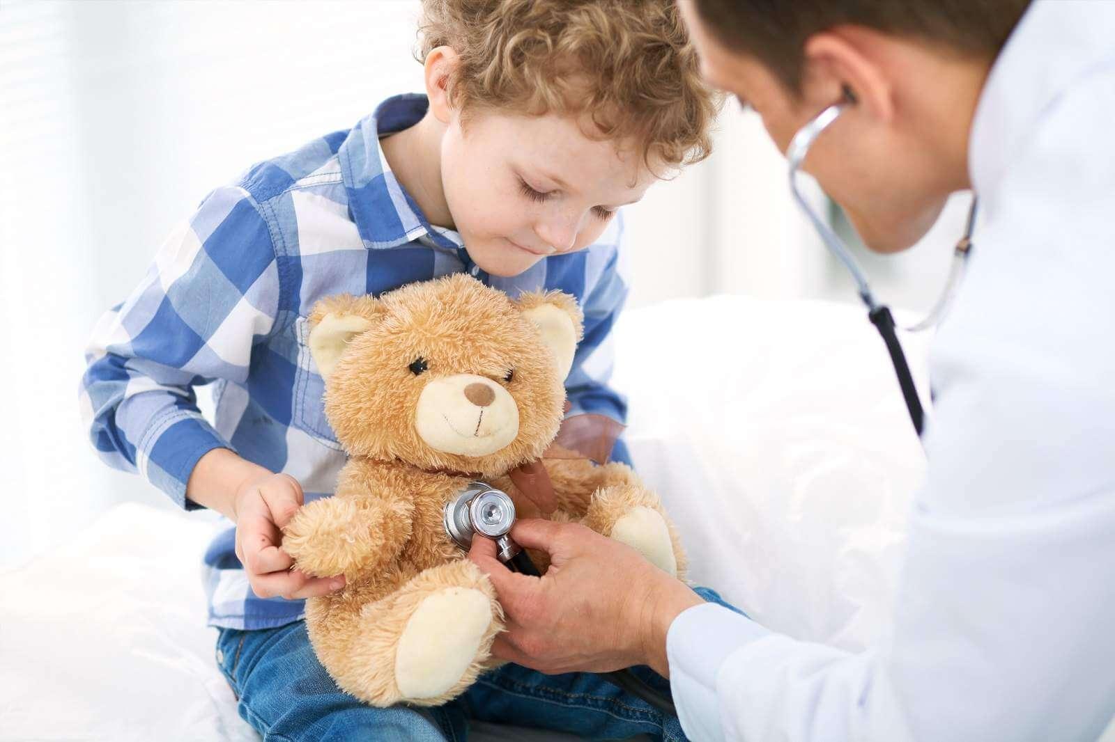 Мальчик на приеме невролога – врач слушает мишку