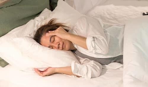 Внезапный приступ мигрени у женщины в постели