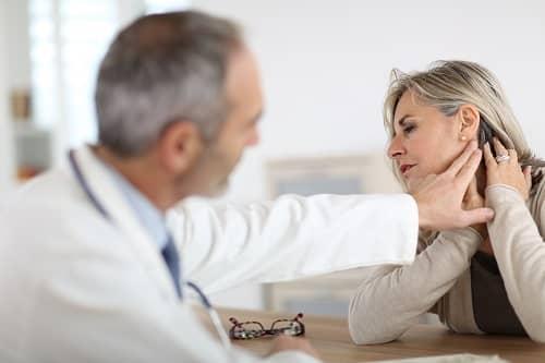 Врач осматривает женщину с шейной мигренью