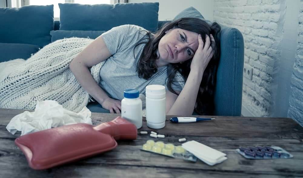 Женщина пытается вылечить приступ мигрени таблетками