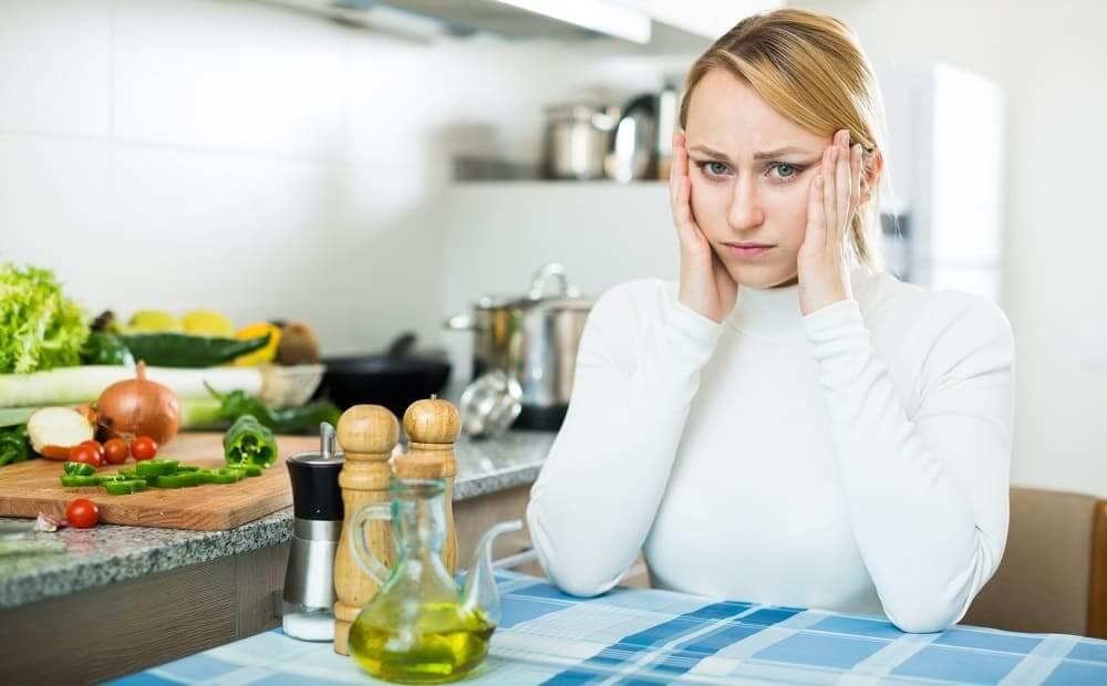 Женщина в кухне с мигренью