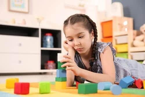 Девочка школьник играет в кубики