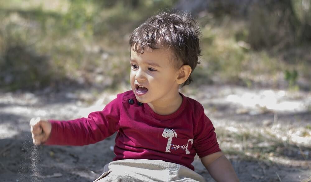 Мальчик 2 лет с СДВГ играет в песке