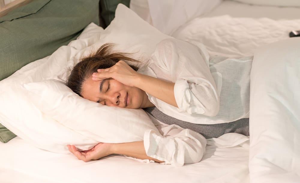 Жещина в постели с утренним приступом мигрени