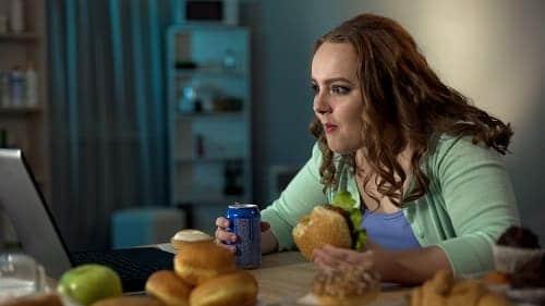 Девушка с нездоровой пищей перед компьютером