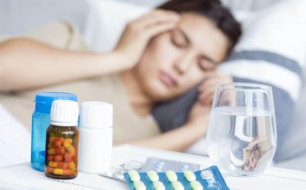 Приступ мигрени у женщины в постели