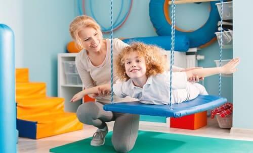 Мальчик в программе реабилитации с тренером