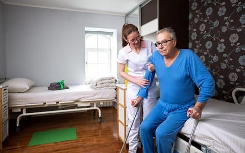 Медик помогает встать мужчине инвалиду