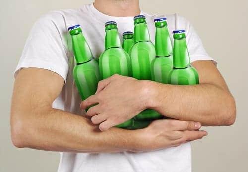 Мужчина держит много бутылок пива