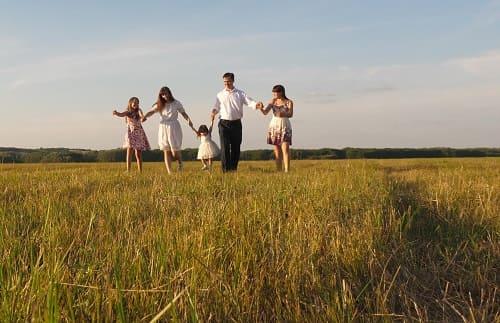 Мужчина с семьей гуляет на природе