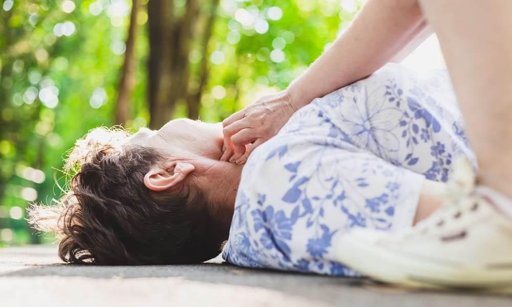 Пожилая женщина на асфальте без сознания