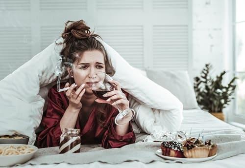 Женщина курит, пьет, нервничает, лежит в постели