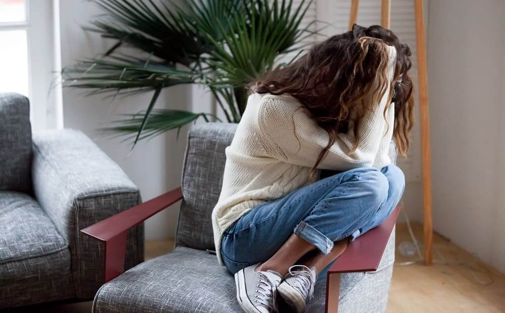 Женщина с симптомами ВСД в депрессии на кресле