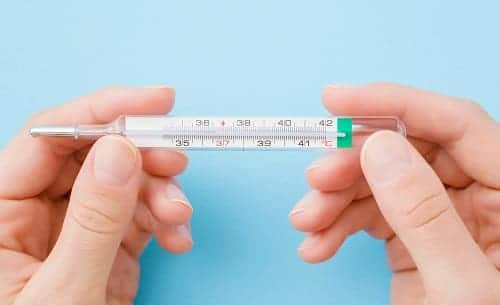 Женские пальчики держат термометр