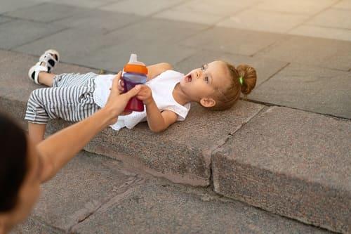Девочка аутист лежит на камнях