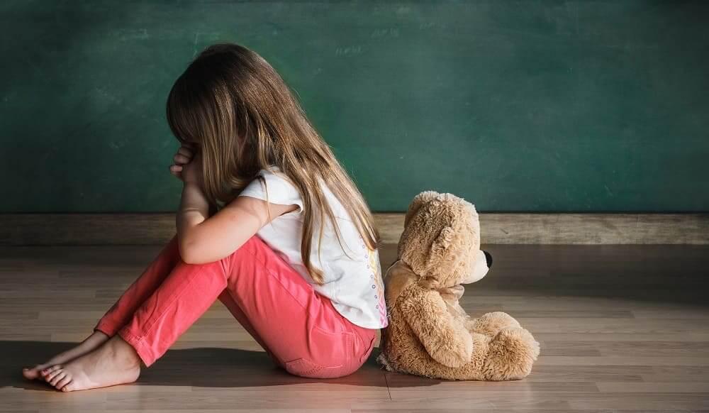 Девочка сидит спиной к игрушке