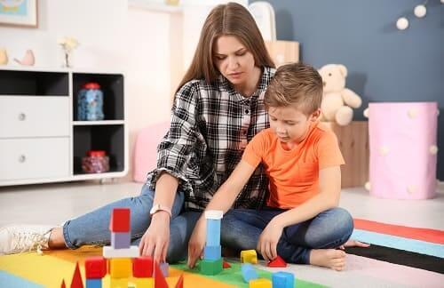 Ребенок аутист играет в игру с мамой