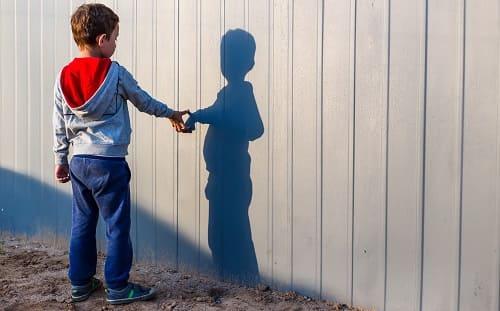 Ребенок играет со своей тенью на заборе