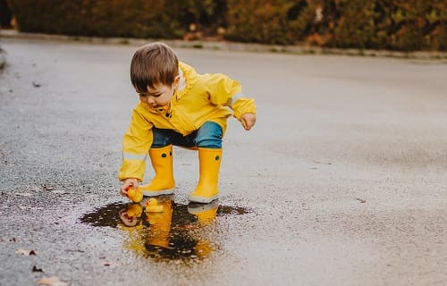 Ребенок играет в луже на дороге