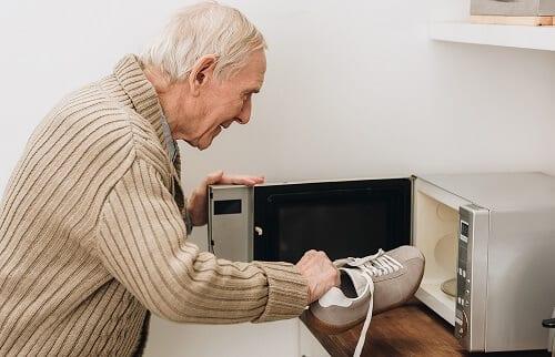 Старик с деменцией сует обувь в печку